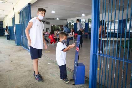 Aluno usa álcool em gel na entrada da Emef Brigadeiro Correa de Melo, em Itaquera, zona leste de SP