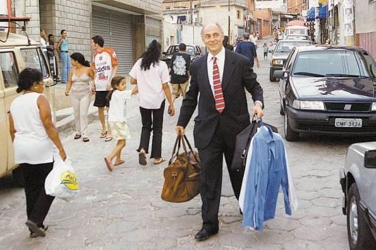 Eduardo Suplicy carrega sacola e cabides com roupas em rua da favela de Heliópolis