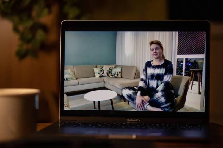 Computador aberto com tela ligada, há imagem de uma mulher sentada em cadeira, na sala de um apartamento