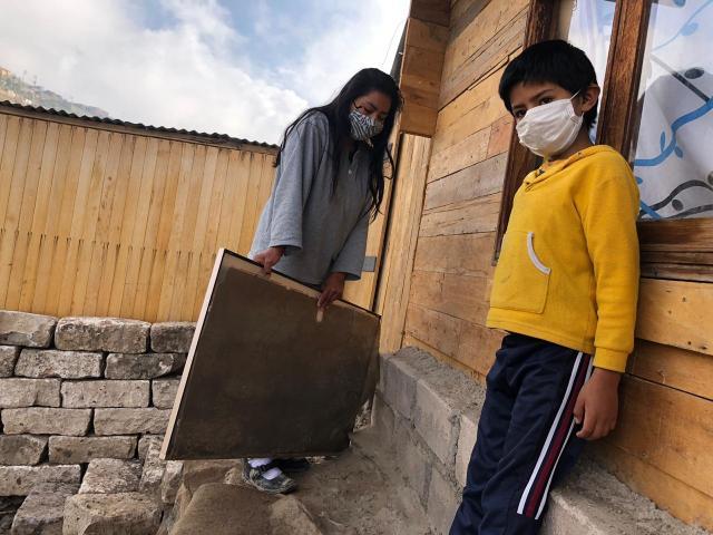 Joven madre y su hijos muestransu televisión dañada tras ingreso de huaico en el sector de Pozo Negro.