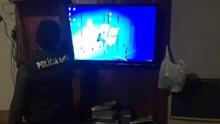 Policial durante ação comandada pela Depca para cumprir mandados contra suspeitos de exploração sexual usando a internet. (Foto: Divulgação/Polícia Civil))