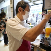 A manager serves alcohol at an izakaya pub in Tokyo on Monday evening. | KYODO