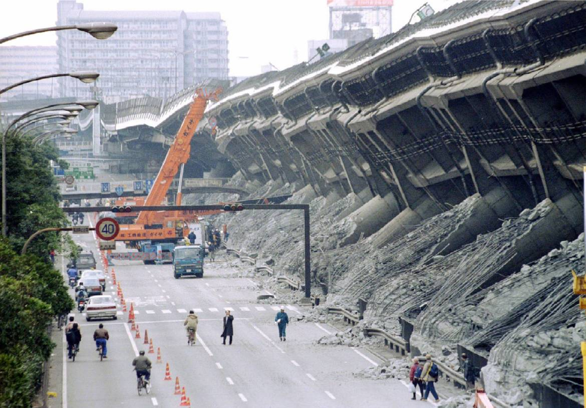 A giant crane pulls crushed cars out of debris in Kobe in January 1995. | REUTERS