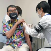 Taro Kono, the Cabinet minister in charge of the vaccine rollout, receives his first COVID-19 vaccination in Tokyo on Monday. | POOL / VIA KYODO