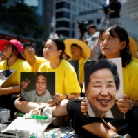 Students hold portraits of deceased former South Korean 'comfort women' during a weekly anti-Japan rally in Seoul in 2018.   | REUTERS