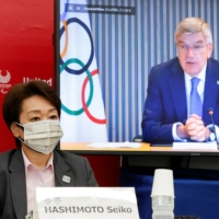 Seiko Hashimoto, President of Tokyo 2020, and IOC President Thomas Bach speak during a five-party meeting in Tokyo on Monday. | POOL / VIA REUTERS