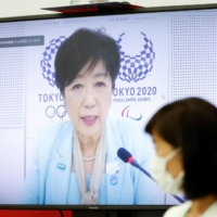 Tokyo Gov. Yuriko Koike (on screen) and Tamayo Marukawa, minister for the Tokyo Olympic and Paralympic Games, speak during a five-party meeting at Harumi Island Triton Square Tower Y in the capital on Monday. | POOL / VIA REUTERS
