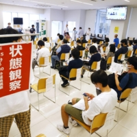 Students sit at a Nippon Sport Science University campus in Tokyo's Setagaya Ward on Monday after receiving a COVID-19 vaccine shot.   KYODO