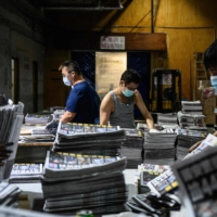 Employees compile different sections of freshly printed papers in the printing facility of the Apple Daily newspaper in Hong Kong on Friday.  | AFP-JIJI