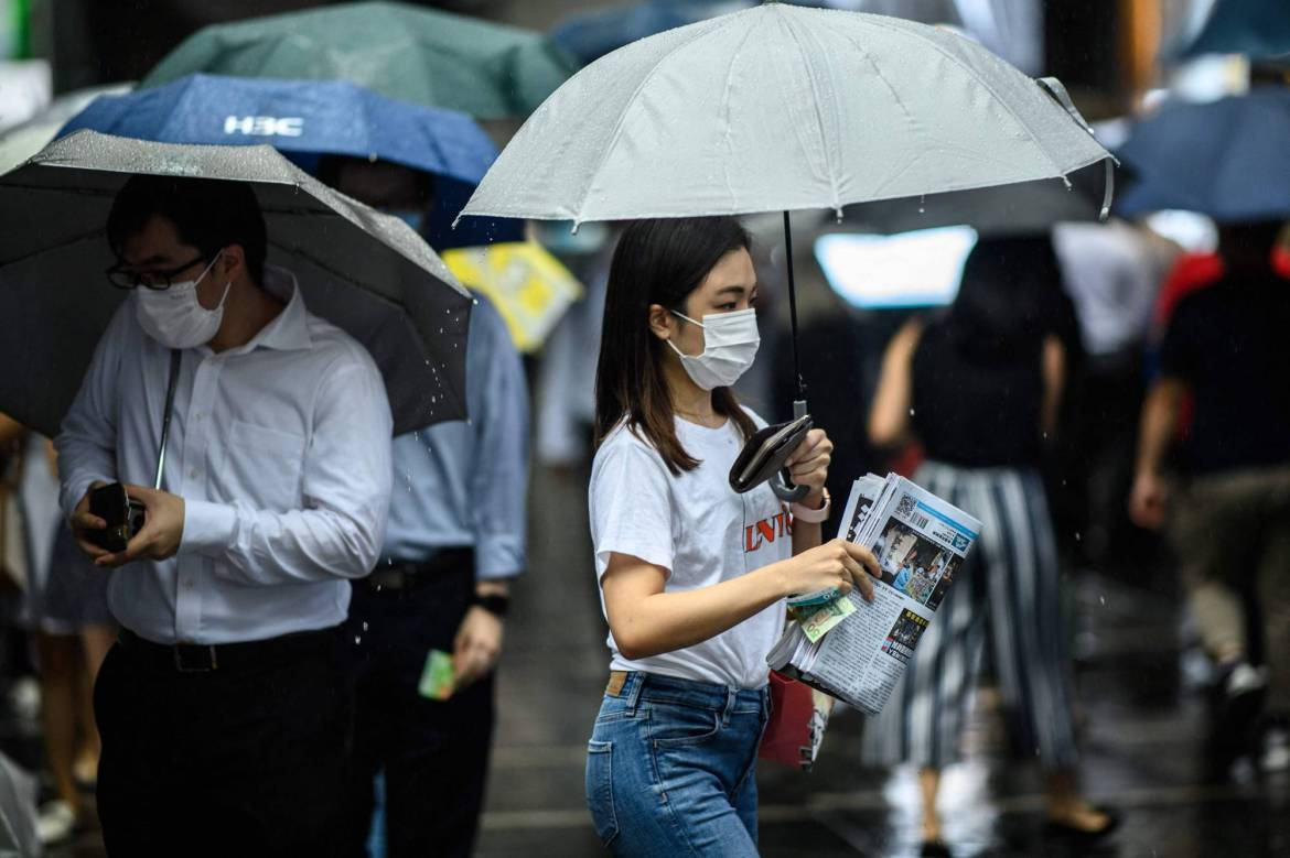 A woman protects her copy of the Apple Daily's final issue from the rain after lining up to buy it from a newsstand in Hong Kong on Thursday. | AFP-JIJI