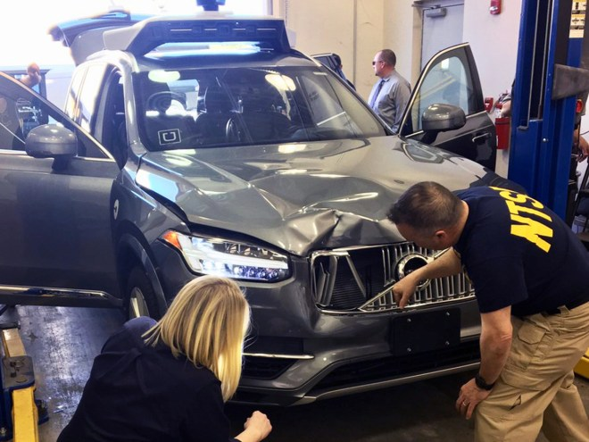 National Transportation Safety Board (NTSB) investigators examine a self-driving Uber vehicle involved in a fatal accident in Tempe, Arizona, U.S