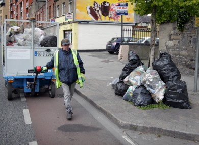 A Dublin City Council employee pictured near illegal rubbish.