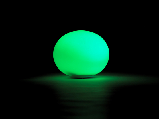 A glowing green orb shines through a dark space.
