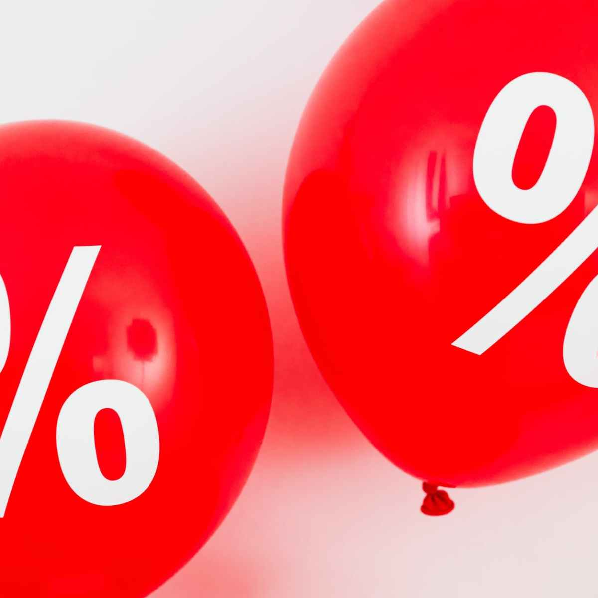 two red balloons with percentage symbols on white background