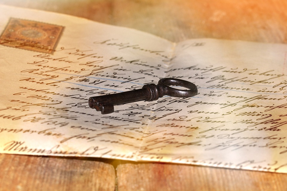 Old handwritten letter on aged wooden surface, with an old house key in the middle of the well folded paper.