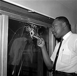 Martin Luther Kings examines bullet in the window