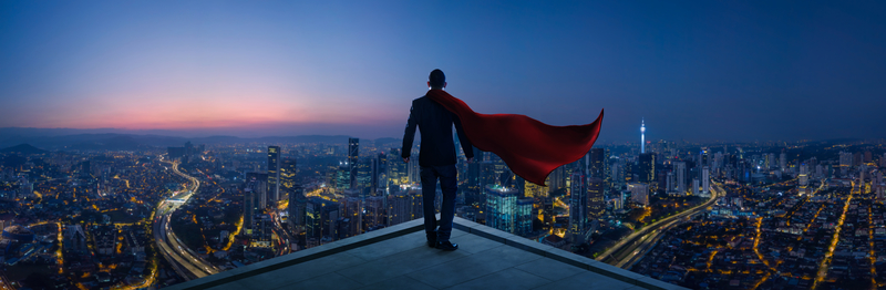 Superhero on building roof looking over city