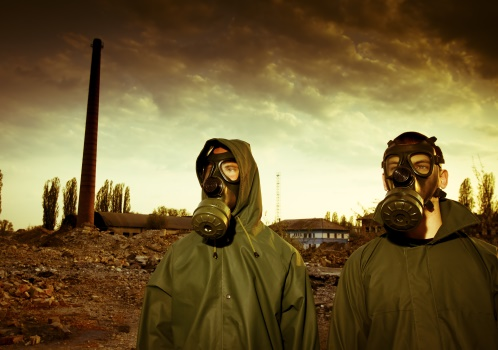 Two men in gas masks against ruined land