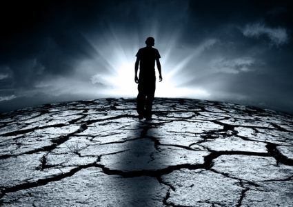 Climate disaster: man walking across a parched ruined land