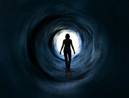 Woman walking in tunnel toward light - Dreamstime_18011521