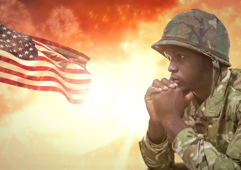 Soldier thinking against sunset and american flag