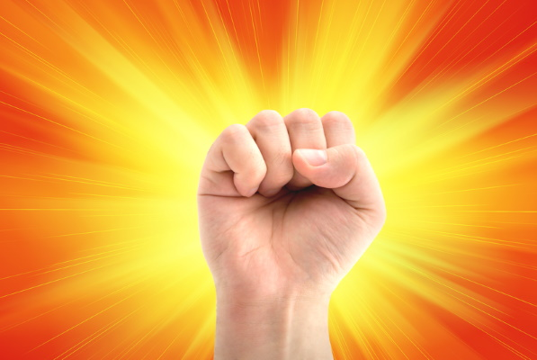 Raised fist of man on sunny background: revolution.
