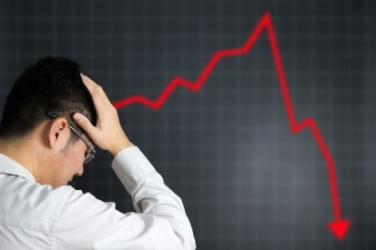 Man in depression looking at graph of economy crashing