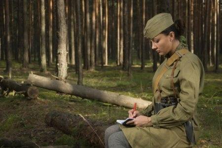Soviet female soldier in uniform of World War II writes