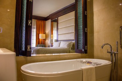 Deep bathtub with a view into the bedroom at The Ritz-Carlton Abu Dhabi