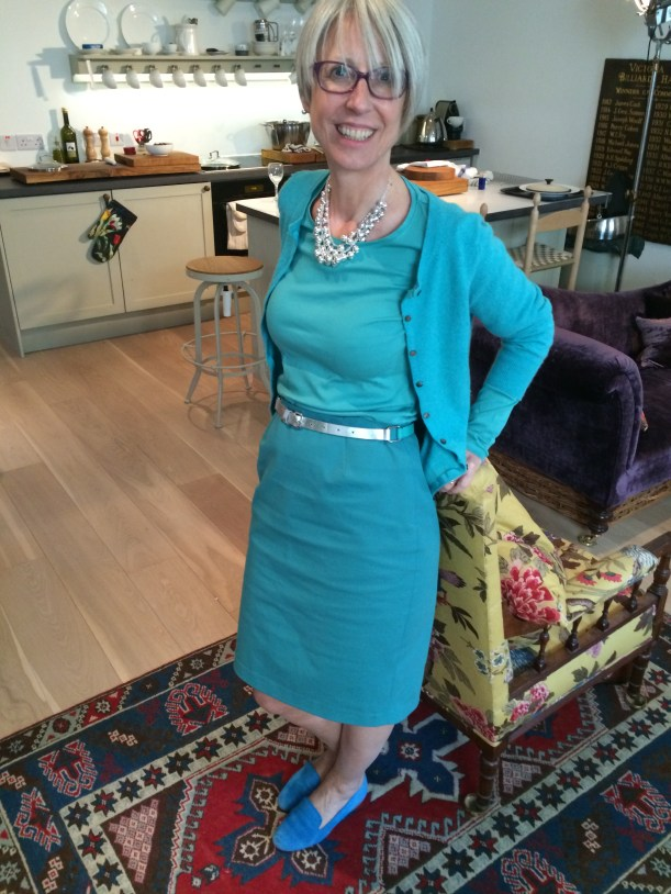 Kate Davies in turquoise skirt, Tshirt and cardigan with blue shoes