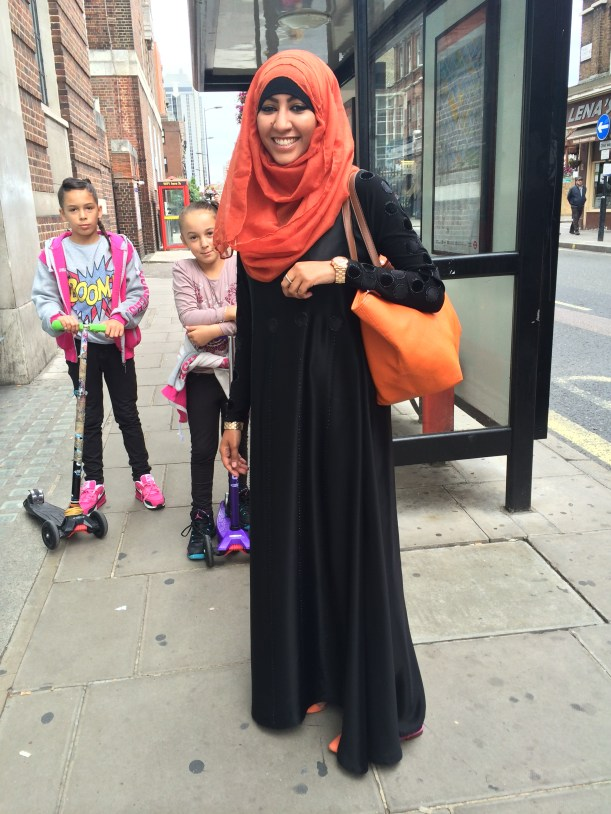 Arabic woman in black dress with orange headscarf and bag