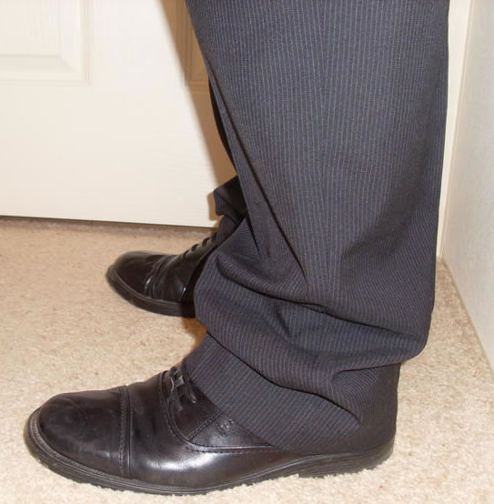 man with black shoes and navy trousers that are too long