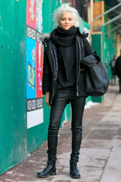 Girl dressed in black next to a green wall