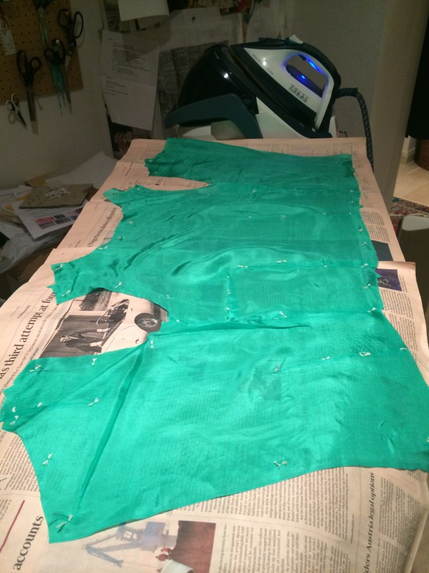 Green silk bodice, pinned to ironing board