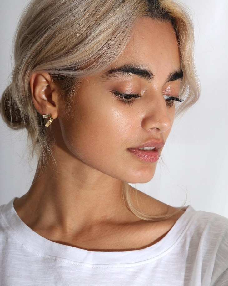 Woman wearing earrings by ANUKA ethical jewellery brand