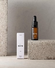 Aire CBD bottle on top of concrete brick, next to product packaging