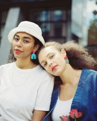 Two women wearing statement hanging earrings