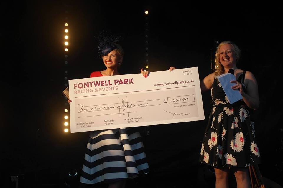 Amy hart at fontwell park collecting prize after winning best dressed competition 2016