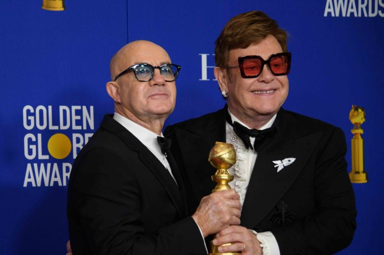 Bernie Taupin and Elton John pose backstage in the press room with the Golden Globe Award