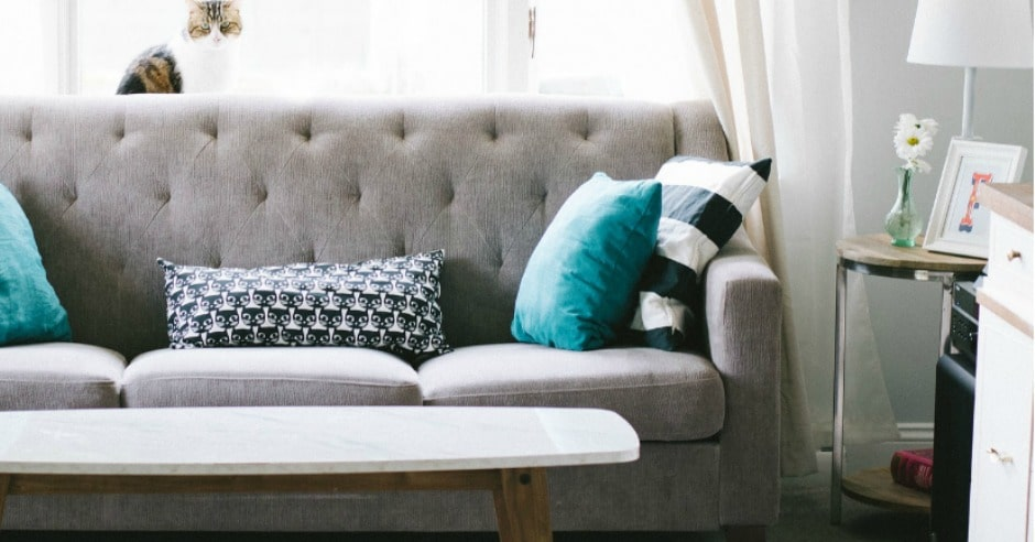 Couch in a living room with pillows and other furniture