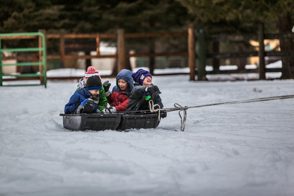 Three kids getting pulled on a sled