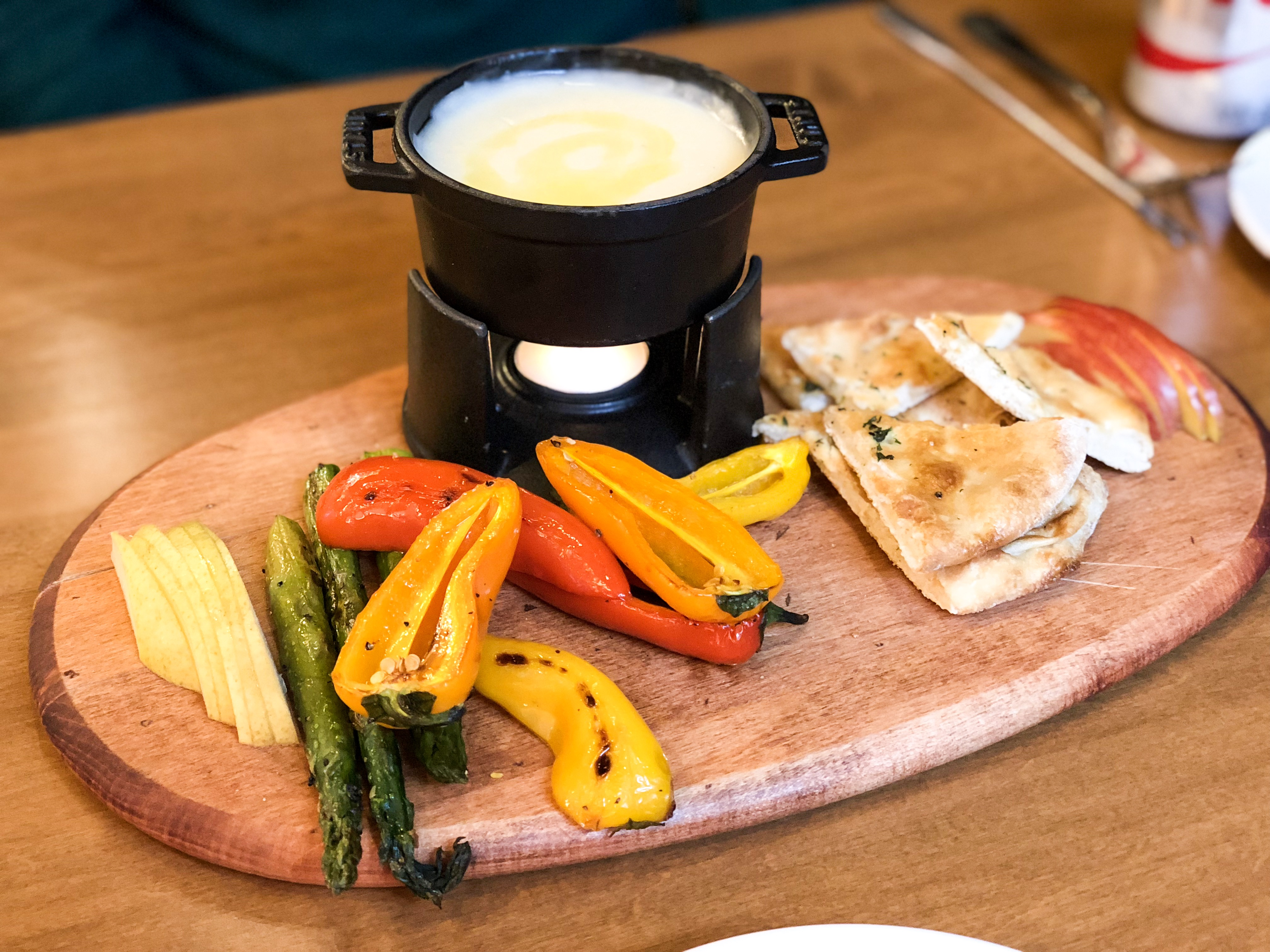 A plate of vegetables and bread with a black fondue pot sitting on a wooden tray