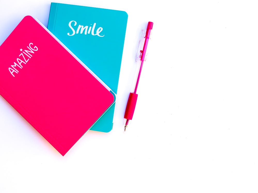 Blue and pink notepads against a white background