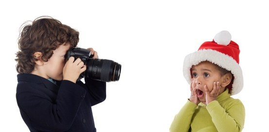 Little photographer making a picture of a baby with Santa Claus hat on a over white background
