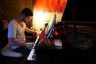 houseguest Karam playing piano
