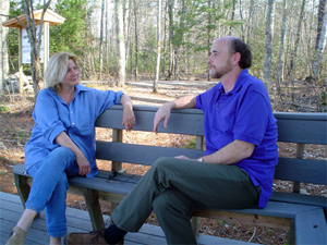 Photo of Carol and Jim outsdie, sitting on a bench - talking.