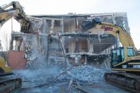 As two big construction vehicles tearing down the backside of the building, dust rises from the skeletal remains of the building.