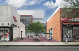 What the Essex Street Plaza would look like after, depicting the fence removed, a new brick ground cover, clean painted or restored building sides, trees and plants, and benches and tables with umbrellas and chairs giving it a clean, inviting look to it.