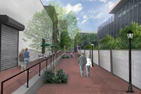 What the School Rear Entrance would look like after, depicting a new stylish fence, new brick walkways, clean painted or restored building sides, trees and plants, street lamp posts, and tables with umbrellas and chairs giving it a clean, inviting look to it.