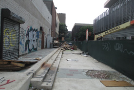 What the School Rear Entrance looks like before with; old and broken sidewalk, garbage dumped all over, dirty or graffiti painted building sides, and a green covered chain link fence.